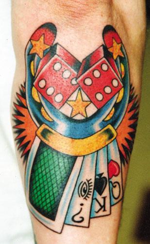 Tatuaje multicolor de una herramienta, unos dados, unos naipes