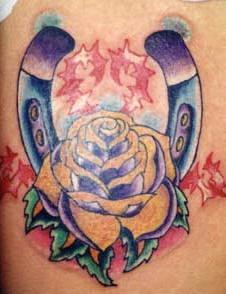 ferro di cavallo con una rosa e spine tatuaggio