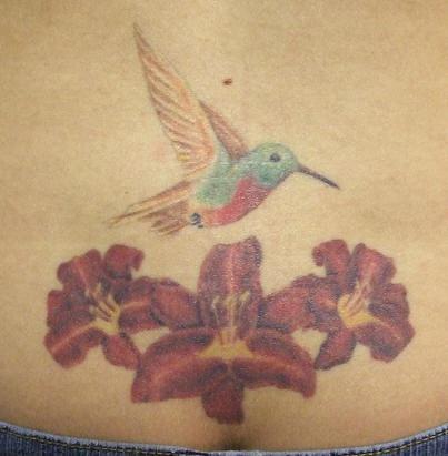 colibri con tre fiori colorati tatuaggio