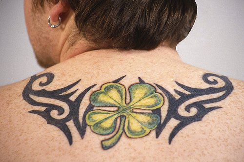 Green four leaf clover and tribal tracery on back