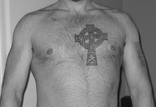 Stone celtic cross tattoo on heart