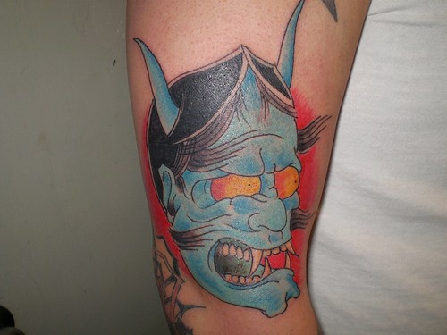Blue japanese demon face tattoo