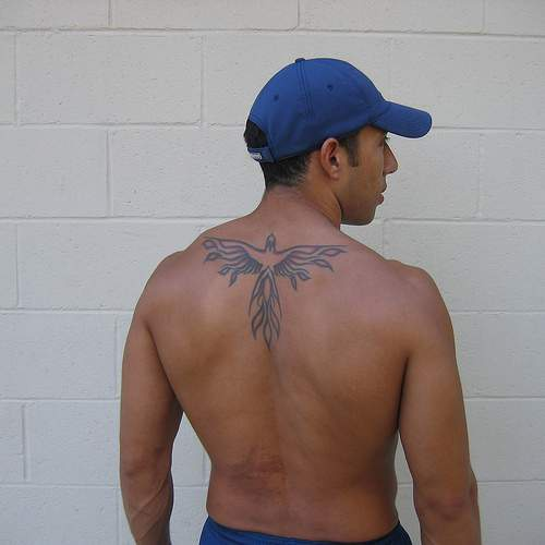 Black phoenix tattoo on upper back