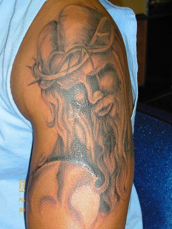 Jesus in crown of thornes tattoo on arm