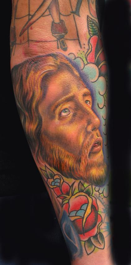 Jesus themed sleeve tattoo in colour