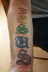 Colourful jesus text tattoo