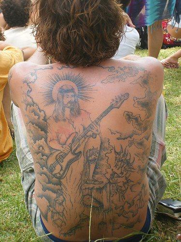 Jesus playing guitar tattoo on back