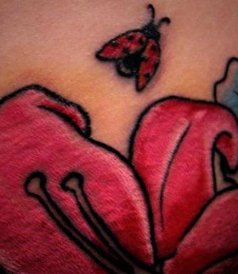 Ladybug on pink flower tattoo