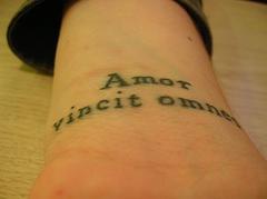Amor vincit omnia tattoo on wrist