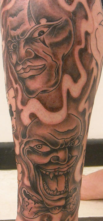 Laughing clowns tattoo on leg