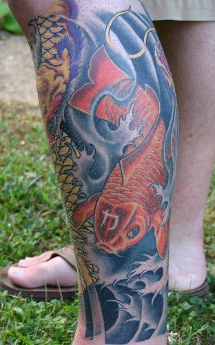 Leg tattoo, big red fish swimming down in water