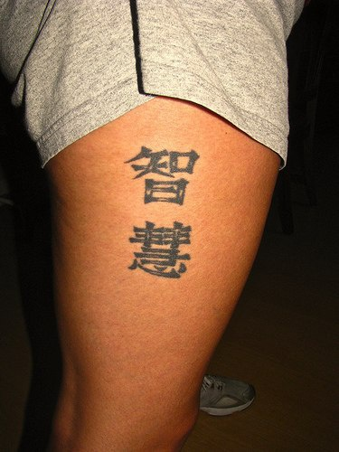 Leg tattoo,two black designed  hieroglyphs