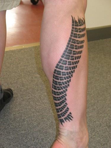 L&quotimmagine della pelle del serpente tatuata sulla gamba