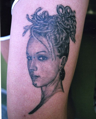 Leg tattoo, beautiful girl with piercing and splitted hair