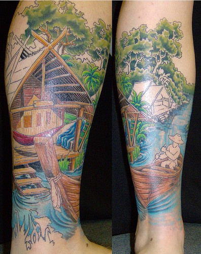 Leg tattoo, country quiet place, man in boat is fishing