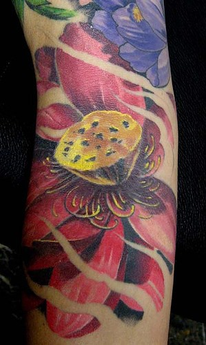 ampio tatuaggio di fiori colorati sul braccio