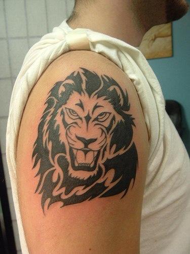 Tribal lion head tattoo on shoulder