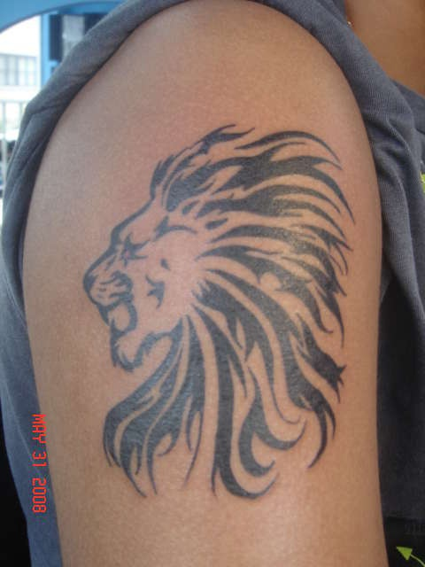 Tribal lion head tattoo on shoulder