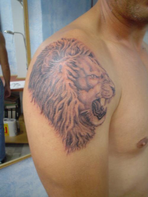 Roaring lion head tattoo on shoulder