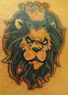 Agressive lion in crown tattoo