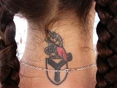 Heraldic shield tattoo on neck