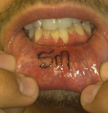 Lip tattoo, sm, two letters, black styled inscription