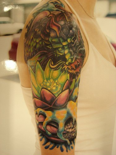 Lotus flower and asian green dragon qualitative tattoo