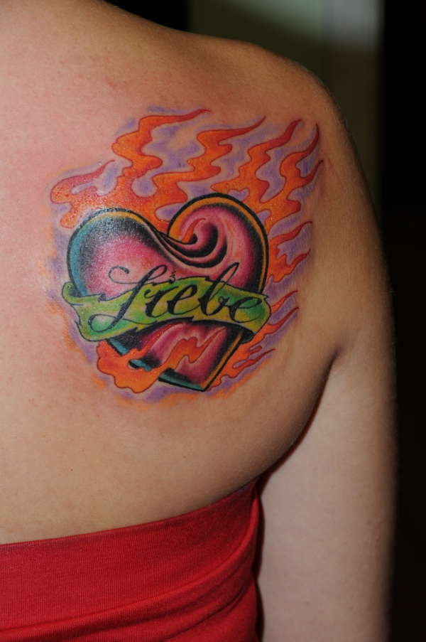 Red heart on flame with lover name tattoo