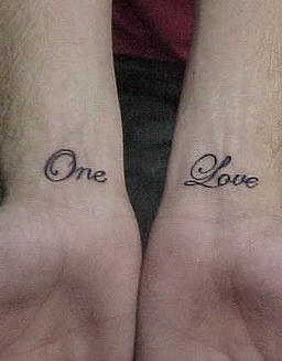 One love writing both wrist tattoo