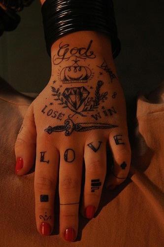 el tatuaje de palabras , una corona , un diamante, un puñal hecho en color negro en toda la mano