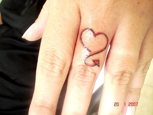 Small devilish heart tattoo on finger