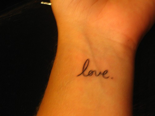 Small love writing tattoo on wrist