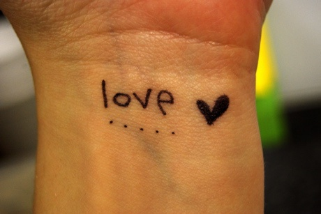 Small love black ink tattoo on wrist