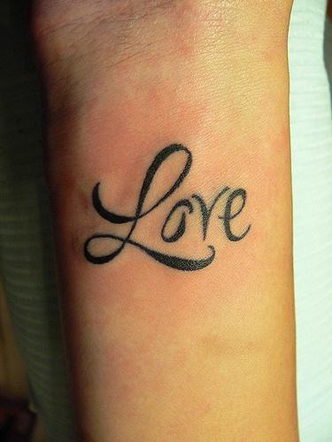 Elegant love lettering wrist tattoo