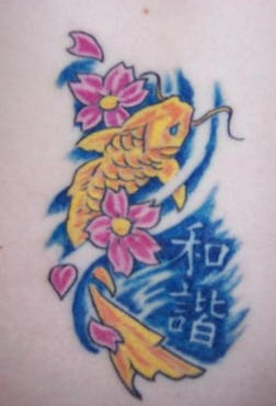 Lower back tattoo, decorated yellow catfish in water, flowers, inscription