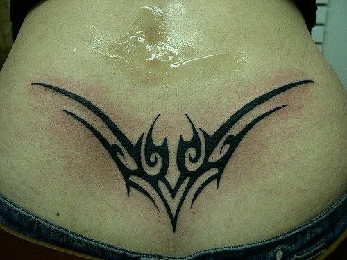 Lower back tattoo, sharp, designed pattern curled