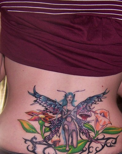 Lower back tattoo, blue, winged  devil fairy,in fine orchids