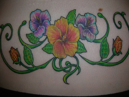 Lower back tattoo, picturesque, big, yellow and violet flowers