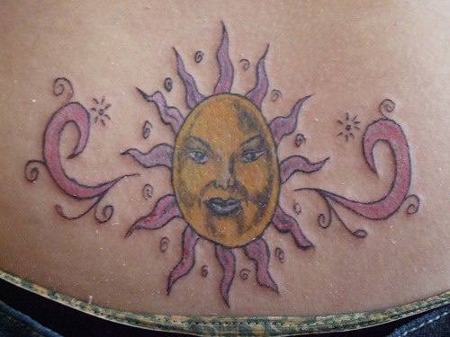 Lower back tattoo, decorated pink and yellow sun