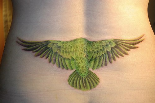 Lower back tattoo, green flying bird, turned back