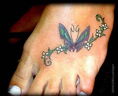 Butterfly on white flowers foot tattoo