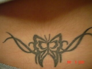 Lower back tattoo, black styled butterfly in curled stripes