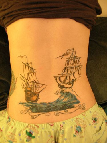 Lower back tattoo, two ships are swimming on waves