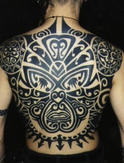 Whole back tattoo of maori tribal face