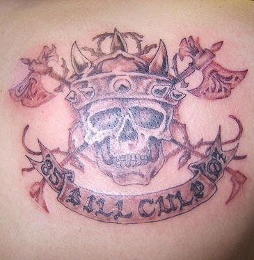 Barbarian skull with weapons tattoo
