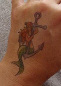 Tatuaggio colorato sulla mano la sirena sull&quotancora