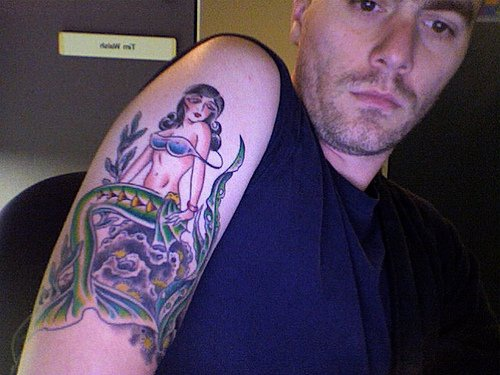 Mermaid on stone tattoo on arm