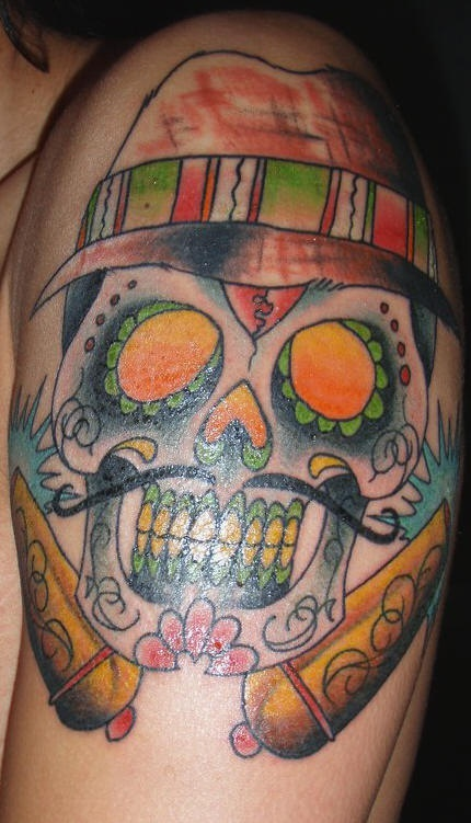 Sugar skull in hat with cannons coloured tattoo