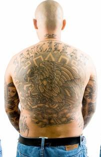 el tatuaje grande  y muy detallado de una aguila en pelea con una serpiente hecho en estilo azteca a toda la espalda