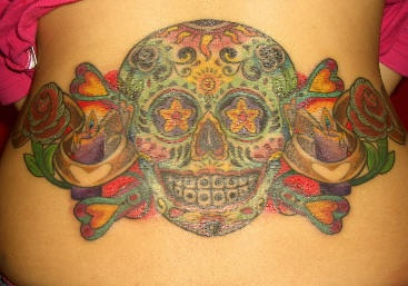 Dia de muertos colourful skull tattoo on lower back